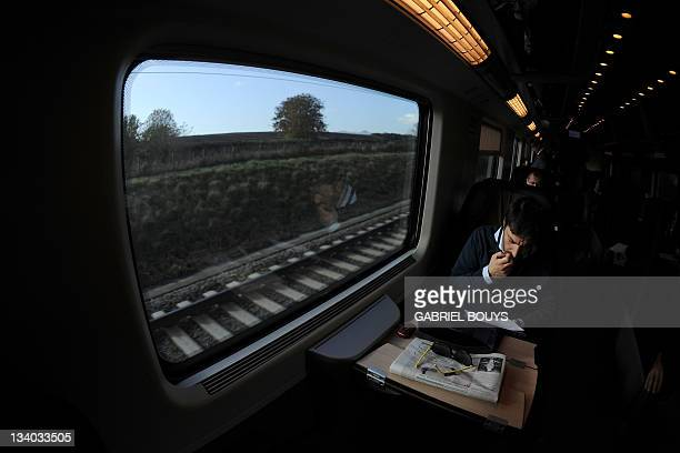 A man reads a newspaper in a Freccia Rossa highspeed train near Naples on November 24 2011 The new Freccia Rossa with four different classes...