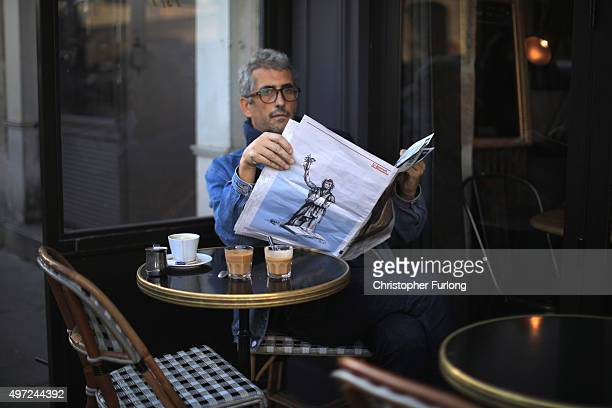 A man reads a newspaper in a parisian cafe as France observes three days of national mourning for the victims of the terror attacks on November 15...
