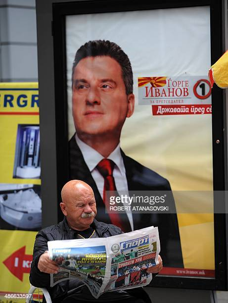 A man reads a newspaper in front of anelection campaign poster of presidential candidate George Ivanov of the ruling VMRO DPMNE party in Skopje on...