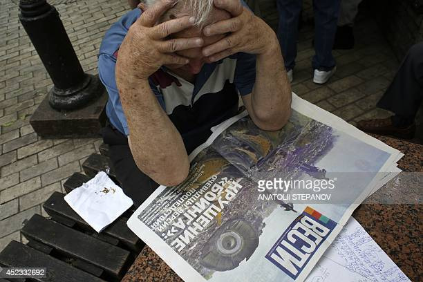 A man reads a newspaper in Kiev on July 18 with front page depicting a plane crash of Malaysia Airlines flight MH17 carrying 295 people from...