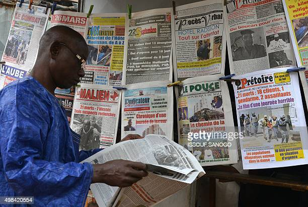 A man reads a newspaper next to a newsstand in Bamako on November 23 three days after a deadly attack at the Radisson Blu hotel Mali started three...