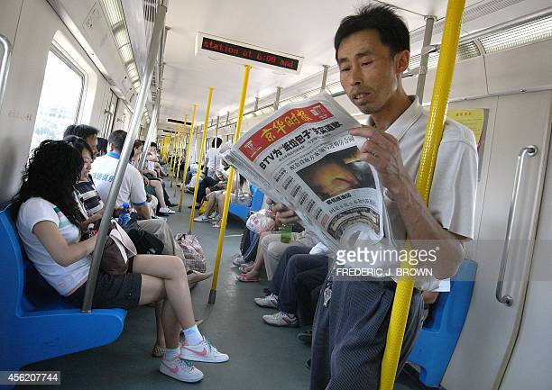 A man reads a newspaper on a Beijing subway line 19 July 2007 with front page news of the plane disaster in Brazil Official data showed China's...