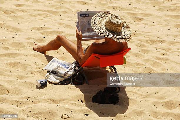 A man reads a newspaper on Balmoral beach as temperatures in Sydney soar well into the 30's and in some regions over 40 degrees centrigrade on...