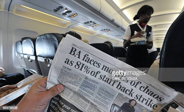 A man reads a newspaper on board of a plane during a flight from London's Heathrow airport on February 23 2010 British Airways cabin crew voted by...