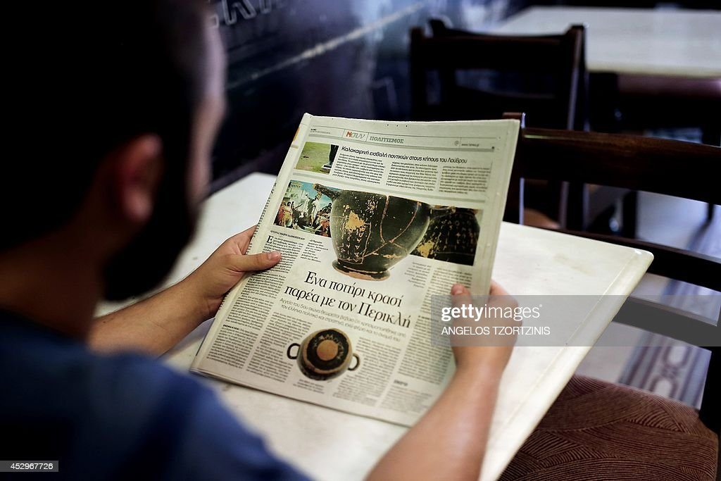 A man reads a newspaper on July 31, 2014 in Athens, showing a cup believed to have been used by Classical Greek statesman Pericles, and which has been found in a pauper's grave in north Athens, Greece's top daily reported on July 30, 2014. The ceramic wine cup, smashed in 12 pieces, was found during building construction in the northern Athens suburb of Kifissia, Ta Nea daily said. AFP PHOTO / Angelos Tzortzinis