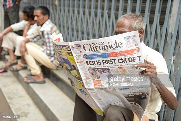A man reads a newspaper reporting on the newlyformed Telangana state's first Chief Minister K Chandra Sekhar Rao taking office in Hyderabad on June 3...