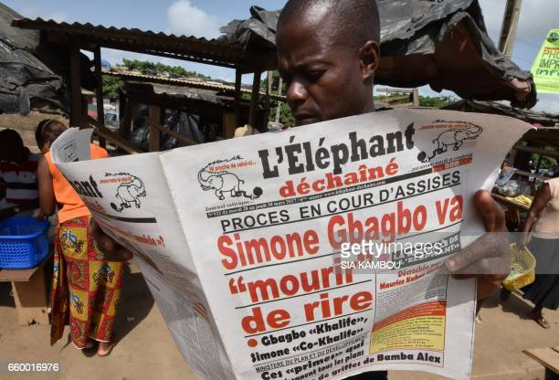A man reads a newspaper reporting the acquittal of former first lady Simone Gbagbo on March 29 2017 in Abidjan one day after an Ivory Coast jury...