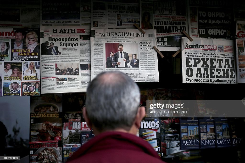 A man reads a newspaper showing Greek Finance Minister Yannis Stournaras, in Athens on April, 3, 2014. Europe needs a 'New Deal' to rise above the economic crisis and austerity policies, the European Left Party's Greek candidate for EU commission chairman, Alexis Tsipras, says in an interview. AFP PHOTO / Angelos Tzortzinis