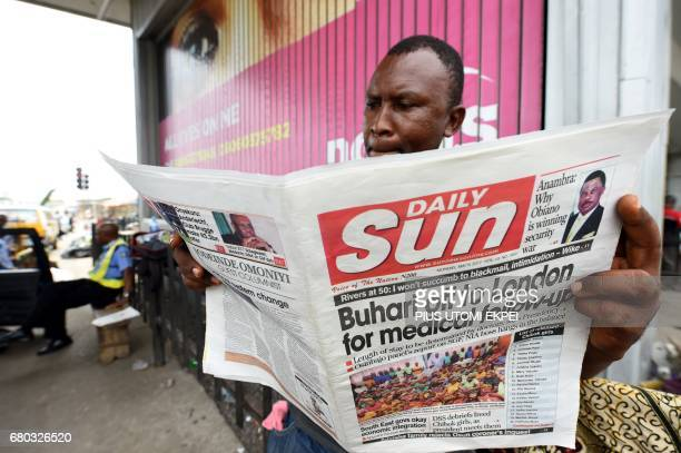 A man reads a newspaper which front page focuses on President Mohammadu Buhari's followup medical consultation in London as he stands outside a...