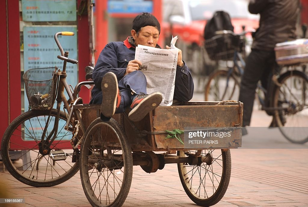 A man reads a newspaper whilst sitting in his tricycle on a street in Shanghai on January 9, 2013. The Southern Weekly, a popular liberal newspaper based in Guangzhou and at the centre of rare public protests about government censorship will publish as usual on January 10, a senior reporter said, following reports of a deal to end a censorship row after hundreds of people demanded greater press freedom after an article urging reforms to uphold people's rights was censored by an official. AFP PHOTO/Peter PARKS