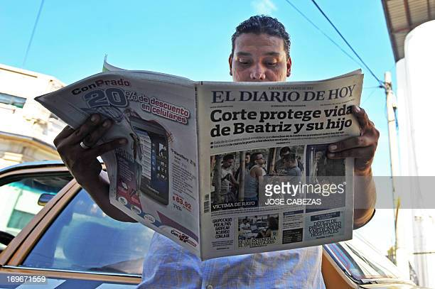 A man reads a newspaper whose front page reads 'Court protects life of beatriz and child' in reference to a woman known as 'Beatriz' hospitalized...