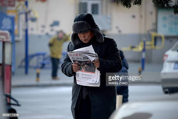 TOPSHOT A man reads a newspaper with a front page headline that reads 'China's GDP grows at 69 percent' while walking along a street in Beijing on...