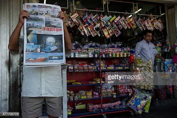 A man reads a newspaper with reports about the missing Malaysia Airlines Boeing 777200 plane in Kuala Lumpur on March 11 2014 Malaysia has expanded...