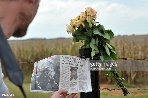 A man reads a page of a newspaper portraiting ANC youth leader Julius Malema as it hangs to the fence next to flowers to pay tribute to African...
