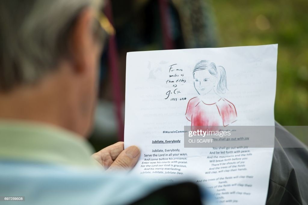 A man reads a song sheet at a 'Great Get Together' community service and picnic in memory of murdered Member of Parliament Jo Cox, marking the first anniversary since her killing, in the grounds of All Saints Church in Batley, northern England on June 18, 2017. The Great Get Together weekend is Inspired by murdered Labour MP Jo Cox's belief that we have more in common than which divides us, a line from her first speech to Parliament, and is a community initiative designed to unite people and communities on the streets and parks of their neighbourhoods. The 41 year-old Labour Party MP, Jo Cox, was assassinated by a pro-Nazi sympathiser in a terror attack in her constituency in northern England on June 16, 2016. /