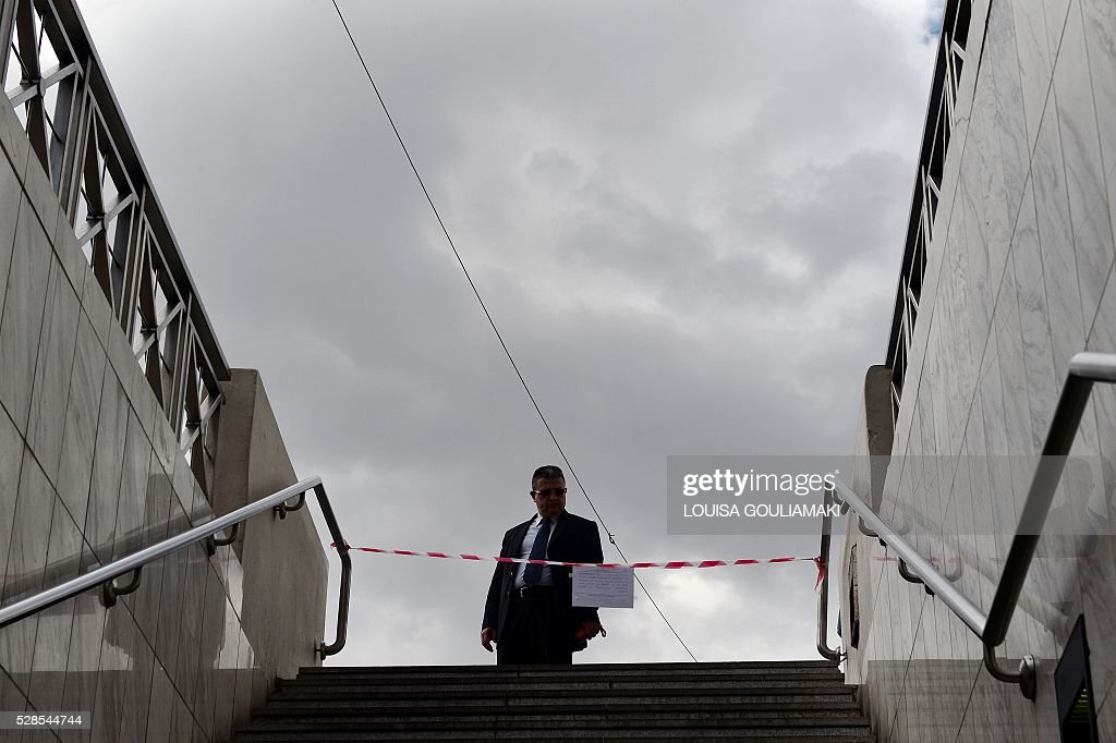 A man reads an announcement informing about 48-hours strike as he stands at a closed metro station in Athens, on May 6, 2016. Greece's labour unions stage a two-day general strike to protest against controversial government plans to overhaul pensions and increase taxes to meet demands of its bailout creditors. / AFP / LOUISA