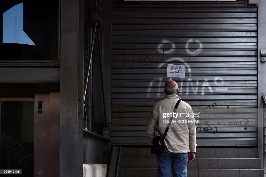 A man reads an announcement while a writing reads 'I m hungry' at a closed urban railway station in Athens, on May 6, 2016, during a 48-hours public transport strike. Greece's labour unions stage a two-day general strike to protest against controversial government plans to overhaul pensions and increase taxes to meet demands of its bailout creditors. / AFP / LOUISA