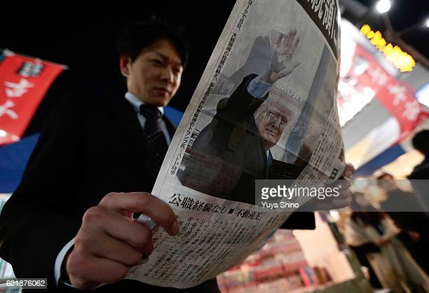 A man reads an extra edition of a newspaper featuring a front page report on the US Presidential Election and Republican Presidentelect Donald Trump...