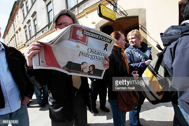 A man reads an polish daily newspaper waiting in the line where tickets to the ceremony of mourning of Polish President Lech Kaczynski and his wife...