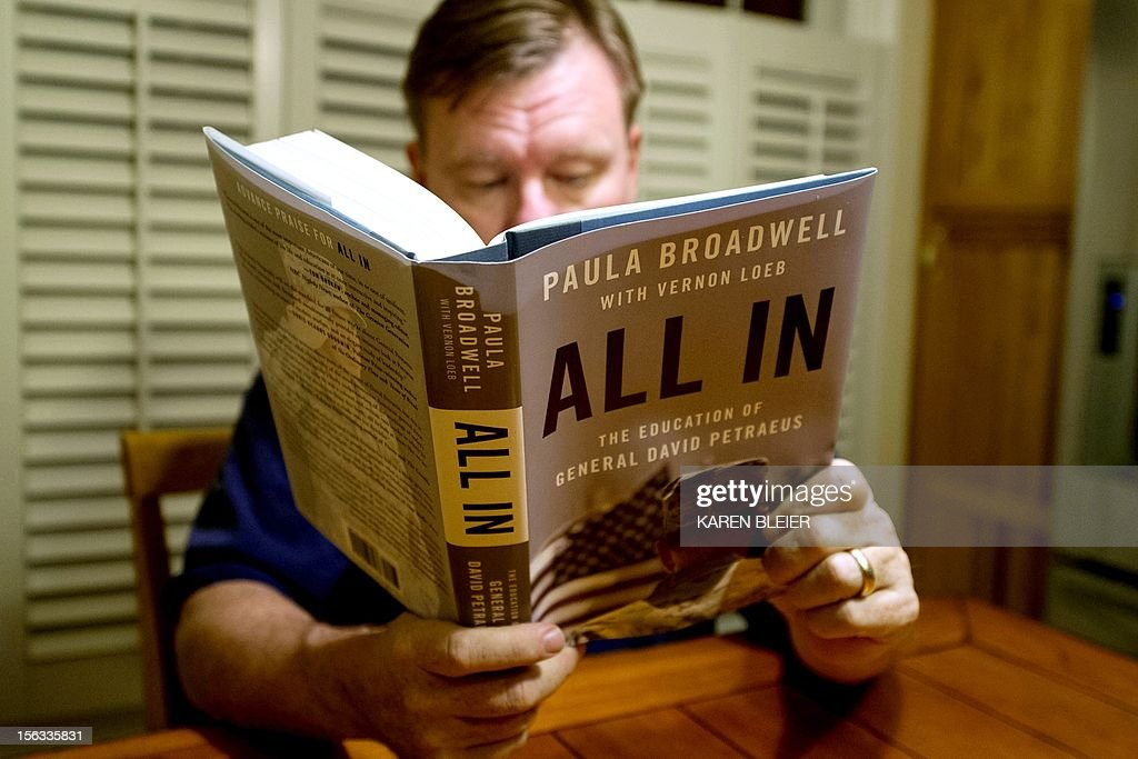 """A man reads biographer Paula Broadwell's book 'All In: The Education of General David Petraeus,' in Manassas, Virginia, on November 13, 2012. Petraeus' surprise resignation as CIA director on Friday resulting from an extramarital affair has now spiraled into a complicated story of infidelity, intrigue and politics. Petraeus' admission of an extramarital affair quickly led to his biographer, Paula Broadwell, and an examination of her relationship with the decorated war hero. The length of the FBI's investigation of """"menacing"""" emails sent to Petraeus' family friend Jill Kelley, and the timing of the announcement of his departure from the Obama administration fueled conspiracy theories. Then Gen. John Allen, Petraeus' successor as military commander in Afghanistan, was embroiled in the scandal, accused by U.S. officials of sending """"inappropriate"""" emails to Kelley. AFP PHOTO/Karen BLEIER"""