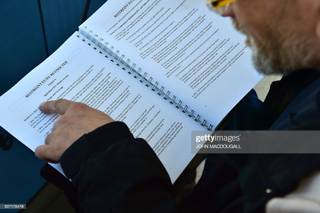 A man reads classified papers from the ongoing US-EU trade talks, presented to the public by Greenpeace near the Brandenburger Gate, in Berlin on May 2, 2016. Greenpeace published documents showing that the Transatlantic Trade and Investment Partnership (TTIP) poses 'major risks for climate, environment and consumer safety'. / AFP / John MACDOUGALL