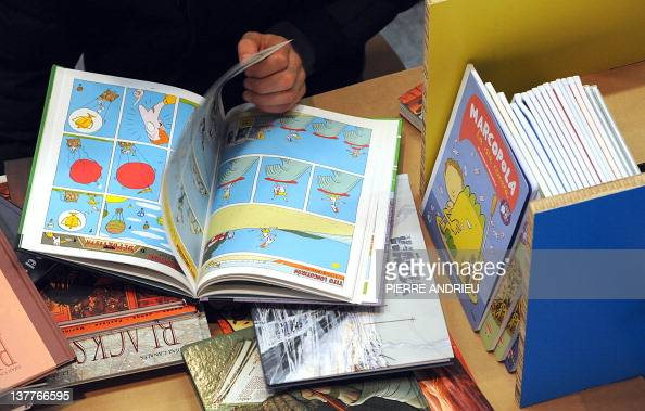 A man reads comics displayed at the 39th edition of Angouleme world comic strip festival headed by American Art Spiegelman on the opening day on...