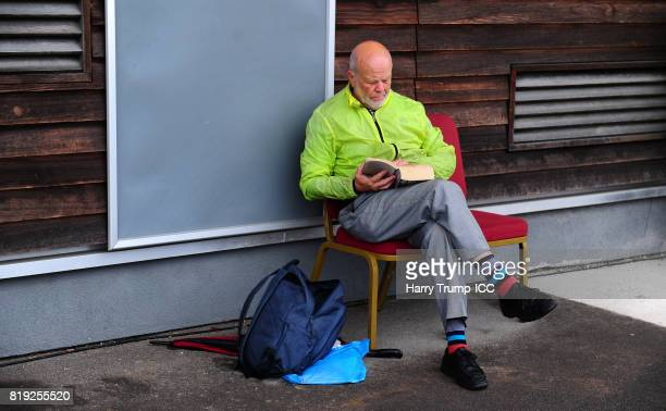 A man reads his book as he waits for play to start during the ICC Women's World Cup 2017 match between Australia and India at The 3aaa County Ground...