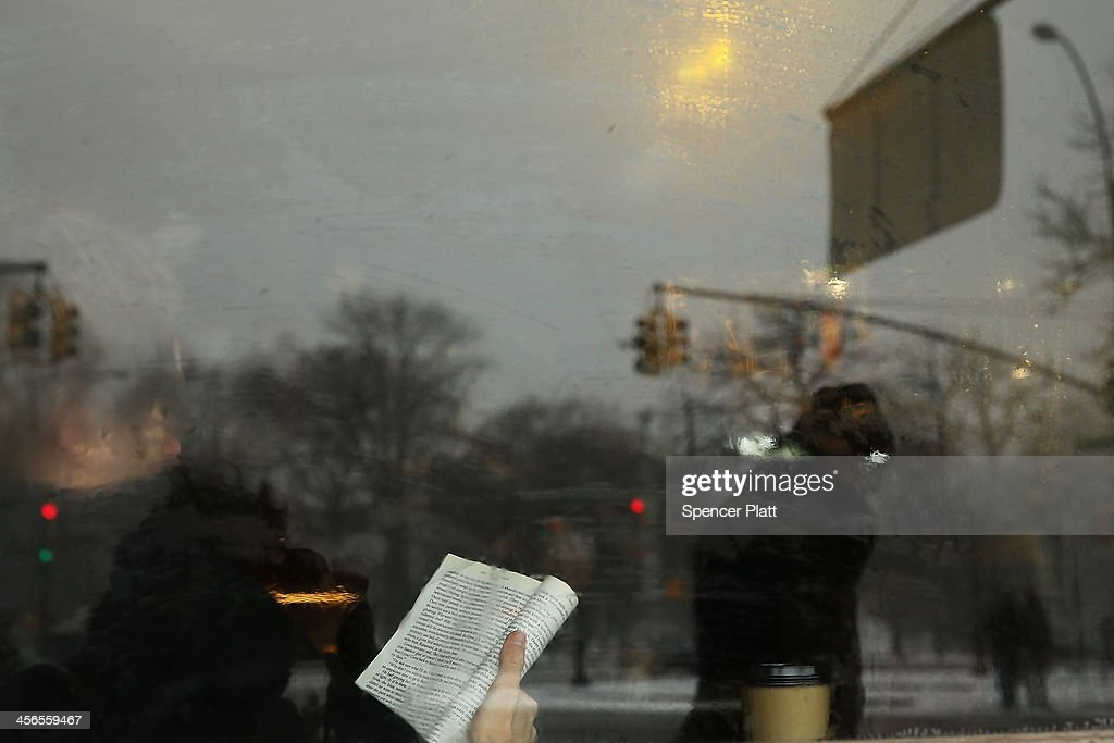 A man reads in a the window of a coffee shop during a snow storm on December 14, 2013 in the Brooklyn borough of New York City. Much of the Northeast was hit by a storm stretching over 1,000 miles that could result in at least a foot of snow on parts of New England.