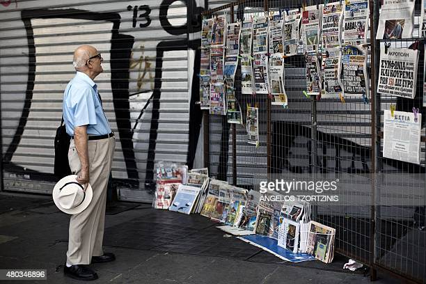 A man reads newspaper headlines at a newsstand in Athens on July 11 2015 Greece's international creditors believe its latest debt proposals are...