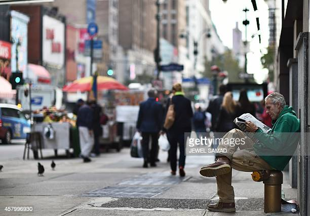 A man reads newspaper on a footpath in New York on October 28 2014 AFP PHOTO/Jewel Samad