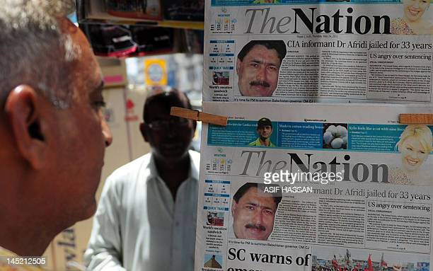 A man reads newspapers bearing photographs of Pakistani surgeon Shakeel Afridi recruited by the CIA to help find Osama bin Laden at a newsstand in...