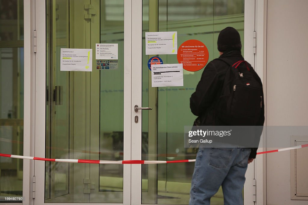A man reads notices at the entrance to a locked Steglitz district branch of Berliner Volksbank following a robbery of the bank that likely occured in the early morning hours on January 14, 2013 in Berlin, Germany. According to police the robbers dug a 30 meter long tunnel from a nearby underground parking garage to access the vault of the bank and made off with the contents.