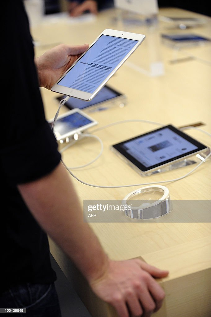A man reads on a new iPad mini during the opening of a new Apple store on November 15, 2012 in Saint-Herblain, western France.