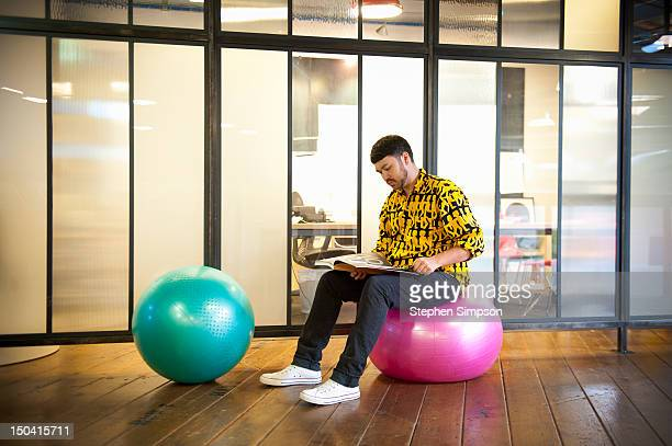 man reads on exercise ball, graphic design office