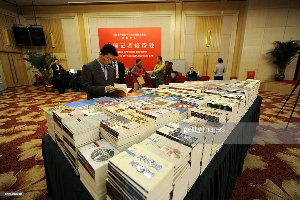 A man reads pamphlets printed by the goverment at the media center for 18th National Congress of the CPC in Beijing on November 1, 2012. The Communist Party's Central Committee convened behind closed doors, state media said on November 1, with 500 senior members to debate key issues ahead of a congress which will open on November 8 to usher in leaders for the next decade.
