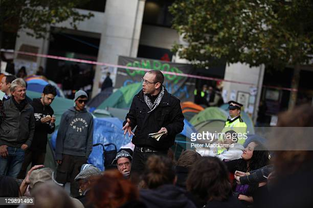 A man reads poetry at The Occupy London protest next to St Paul's Cathedral on October 21 2011 in London England Protestors who are targeting the...