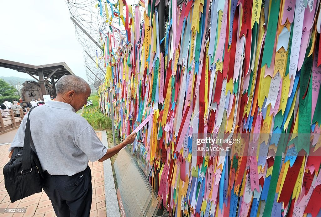 A man reads pro-unification messages on a military barbed wire fence at Imjingak peace park in Paju, near the demilitarized zone dividing the two Koreas on July 27, 2012, on the day of the 59th anniversary of signing the Korean War armistice. The armistice agreement on July 27, 1953 brought three years of active combat in the Korean War to a halt, but the two Koreas are still technically at war as no formal peace treaty was signed. AFP PHOTO / JUNG YEON-JE