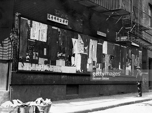 A man reads standing in front of a community bulletin board on Oxford Street in the Chinatown neighborhood of Boston on May 1 1931 The wall has local...