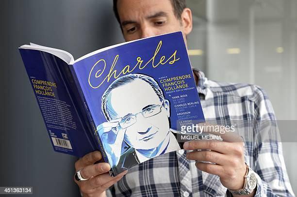 A man reads the book 'Charles number 8 To understand Francois Hollande' on which is depicted a drawing of the French President on June 28 2014 in...