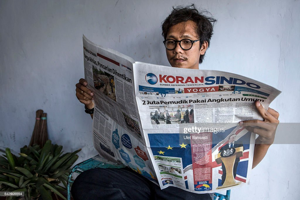 A man reads the Indonesian newspaper KORAN SINDO which shows the cover headline which reads 'British looked at new era', on June 25, 2016 in Yogyakarta, Indonesia. The results from the historic EU referendum has now been declared and the United Kingdom has voted to LEAVE the European Union.