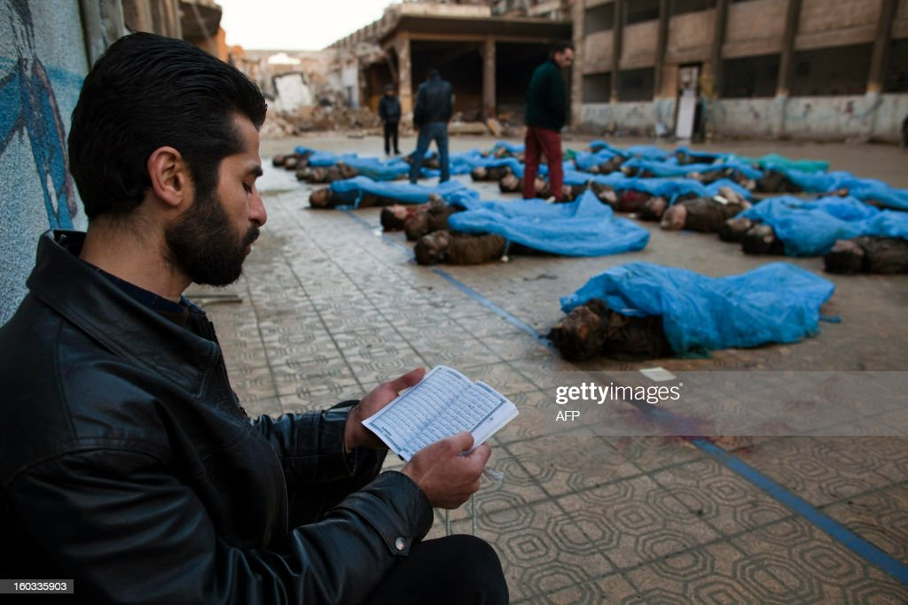 A man reads the Koran next to the bodies of Syrian civilians executed and dumped in the Quweiq river, in the grounds of the courtyard of a Yarmouk School, in the Bustan al-Qasr district of Aleppo, on January 29, 2013. The bodies of at least 65 young men, all executed with a single gunshot to the head or neck, were found in a river in Aleppo city, adding to the grim list of massacres committed during Syria's 22-month conflict.