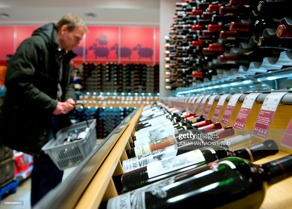 A man reads the labels on red wine bottles displayed in one of the government controlled Systembolaget liquor stores in downtown Stockholm on December 19, 2013. Systembolaget is the only retail store allowed to sell alcoholic beverages that contain more than 3.5 percent (by volume) alcohol. According to Systembolaget, it has a nationwide retail network of 422 stores and over 500 agents serving smaller communities.