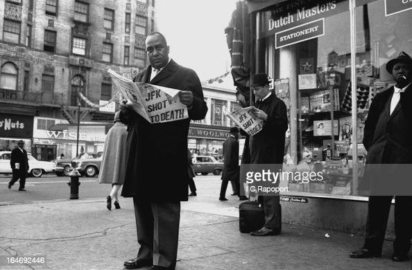 A man reads the latest edition of the NY Post on the evening of the assassination of President John F Kennedy on a street corner of 125th Street in...