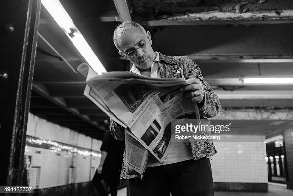 A man reads The New York Times newspaper May 10 2014 while waiting for a subway in New York City