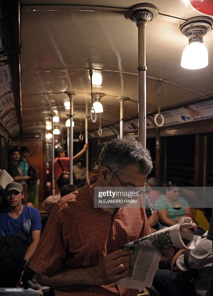 A man reads the newspaper as he travels in one of the historic wagons of La Brugeoise of the subway Line A which is expected to be close soon following a decision by city mayor Mauricio Macri to replace the fleet with Chinese-made wagons, in Buenos Aires, on December 29, 2012. Line A was the first subway line to work in the southern hemisphere and its trains are among the ten oldest still working daily. The La Brugeoise wagons were constructed between 1912 and 1919 by La Brugeoise et Nicaise et Delcuve in Belgium. AFP PHOTO / ALEJANDRO PAGNI --- MORE PICTURES IN IMAGE FORUM