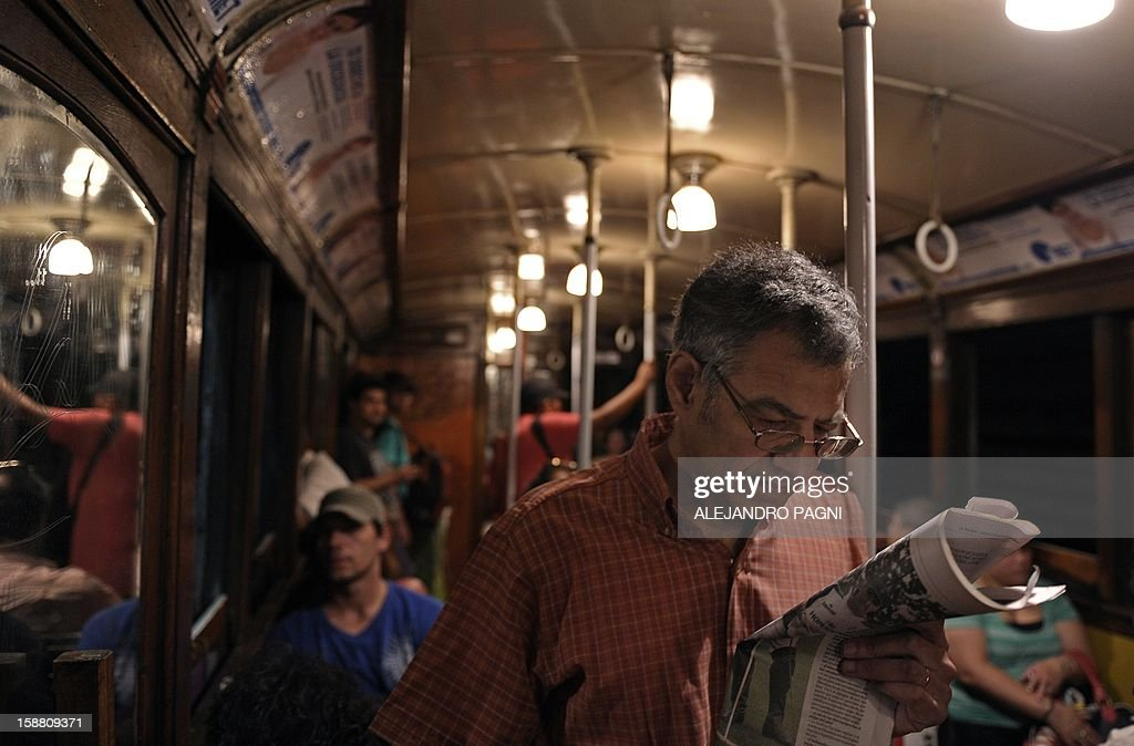 A man reads the newspaper as he travels in one of the historic wagons of La Brugeoise of the subway Line A which is expected to be close soon following a decision by city mayor Mauricio Macri to replace the fleet with Chinese-made wagons, in Buenos Aires, on December 29, 2012. Line A was the first subway line to work in the southern hemisphere and its trains are among the ten oldest still working daily. The La Brugeoise wagons were constructed between 1912 and 1919 by La Brugeoise et Nicaise et Delcuve in Belgium. AFP PHOTO / ALEJANDRO PAGNI