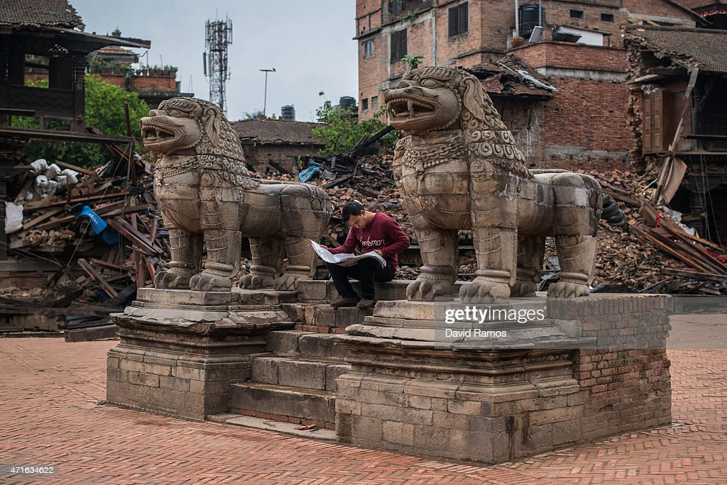 A man reads the newspaper at Durbar square in Bhaktapur on April 30 2015 in Kathmandu Nepal A major 78 earthquake hit Kathmandu midday on Saturday...
