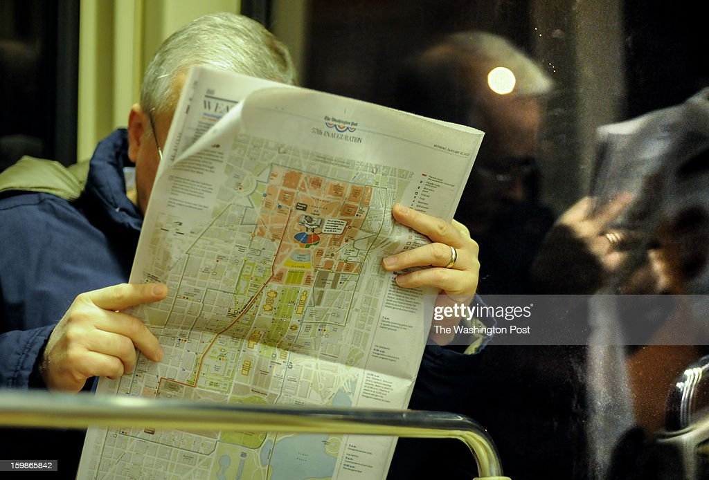 A man reads the newspaper displaying a map of the National Mall during Inaugural activities. January, 21, 2013 in Washington, DC.