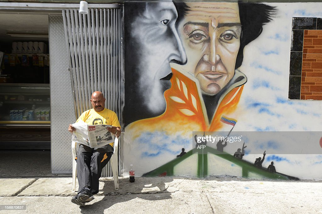A man reads the newspaper next to a graffiti depicting Venezuelan President Hugo Chavez (L) and South American independence hero Simon Bolivar, in Caracas, on January 2, 2013. Chavez is conscious and fully aware of how 'complex' his condition remains three weeks after difficult cancer surgery in Havana, the Venezuelan president's handpicked successor, Vice President Nicolas Maduro, said Tuesday. Chavez underwent his fourth cancer-related surgery three weeks ago in Havana and has been bed-ridden ever since. AFP PHOTO/LEO RAMIREZ