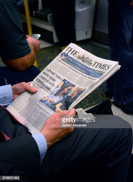 A man reads The Times newspaper as he rides the tube in London England